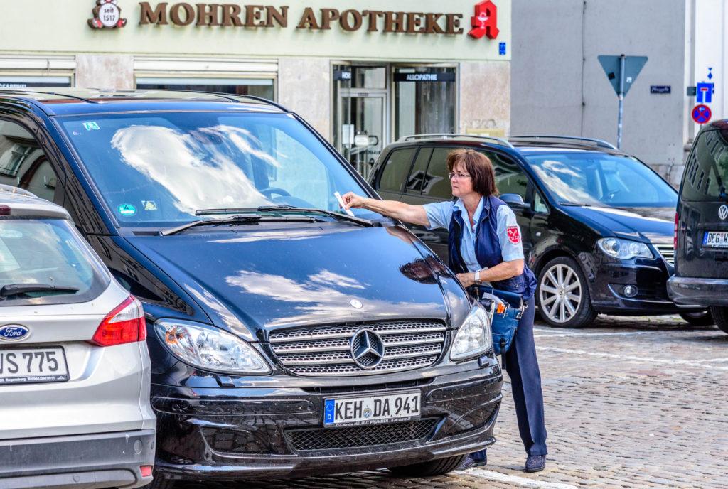 ドイツの基本情報 駐車違反切符を車に置く女性