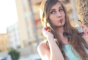 留学保険 プロトリップ ワールド サングラスを口にくわえてぽーすを取る女性