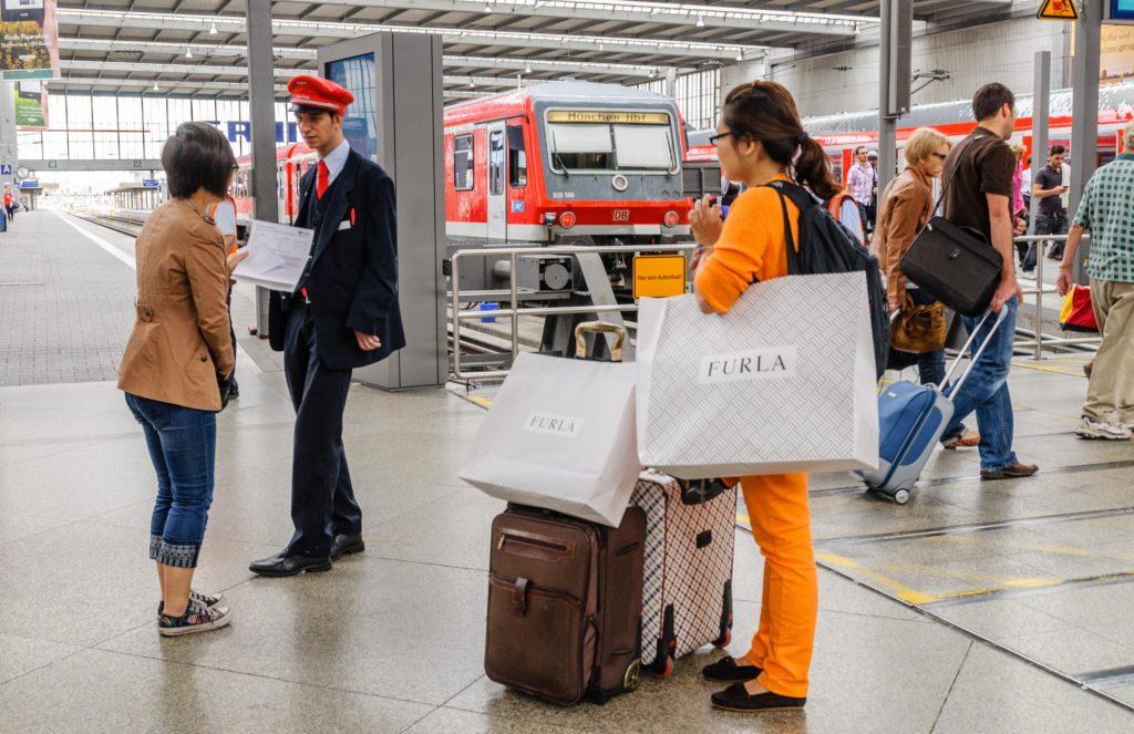 駅で電車の発着を訪ねる観光客